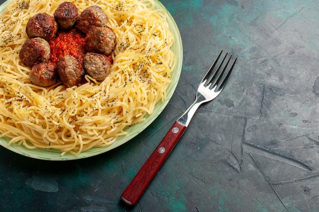 Вид сверху вкусной итальянской пасты с фрикадельками и томатным соусом на темно-синей поверхности