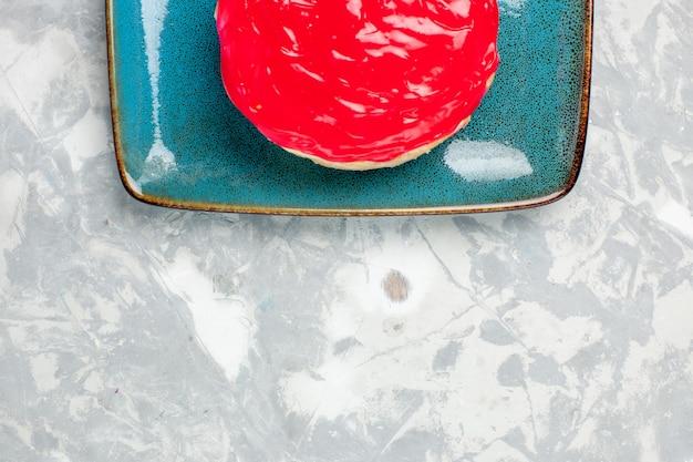 Сверху крупным планом вкусный торт маленький пирог с красным кремом на белой поверхности
