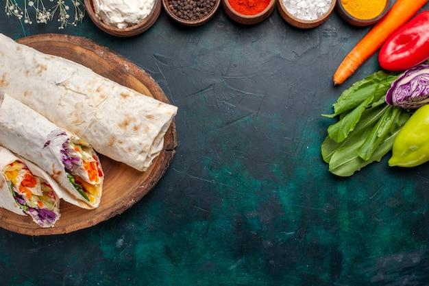 青い机の上に調味料と野菜をつばで焼いた肉で作ったおいしいミートサンドイッチを上から見る