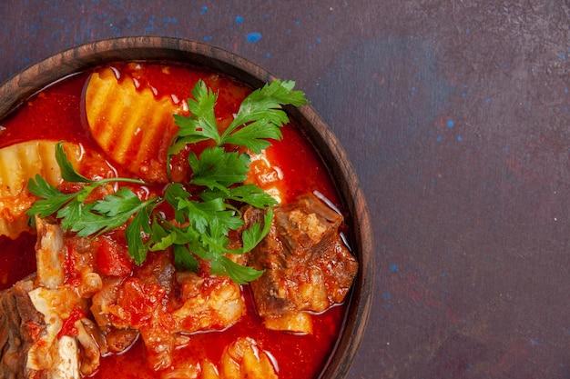 Vista ravvicinata deliziosa salsa di carne con verdure e patate a fette su salsa di superficie scura zuppa pasto cibo piatto per la cena