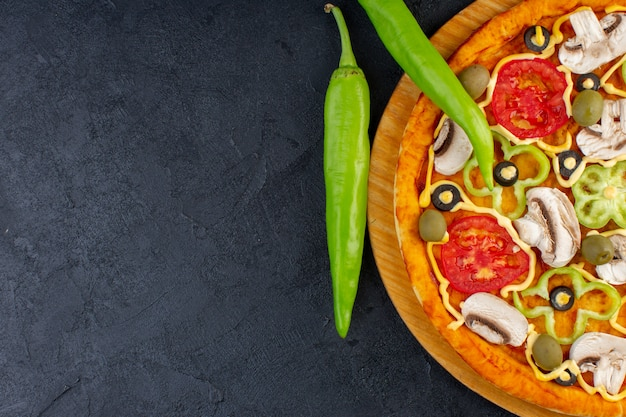 Top close view delicious mushroom pizza with red tomatoes bell-peppers olives and mushrooms all sliced inside on the dark background food pizza italian