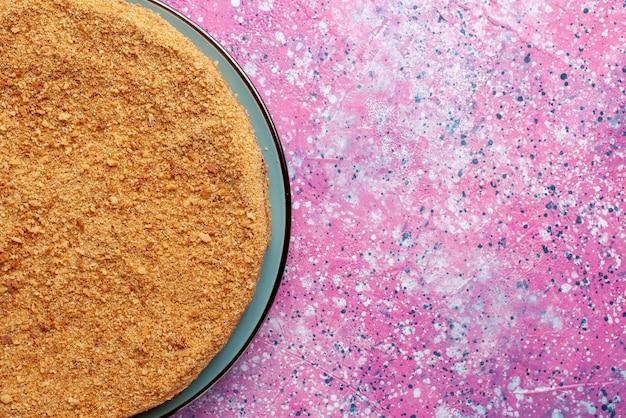 Сверху крупным планом вкусный круглый торт внутри стеклянной тарелки на ярком столе, пирог, бисквит, сладкая выпечка, сахар