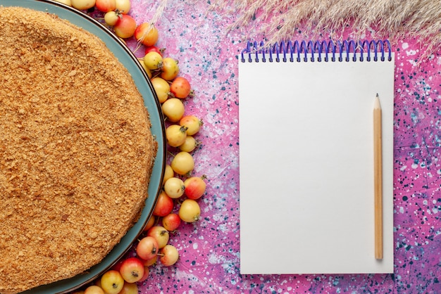 明るいピンクのデスクケーキパイビスケットスイートベイクシュガーに甘いチェリーのメモ帳が並んだプレートの内側のおいしい丸いケーキを上から見る