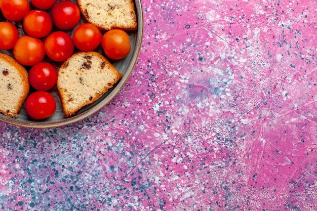 上部のクローズビューピンクの壁のパイ甘い砂糖焼きビスケットクッキーフルーツの鍋の中に酸っぱい新鮮なプラムとおいしいスライスケーキ
