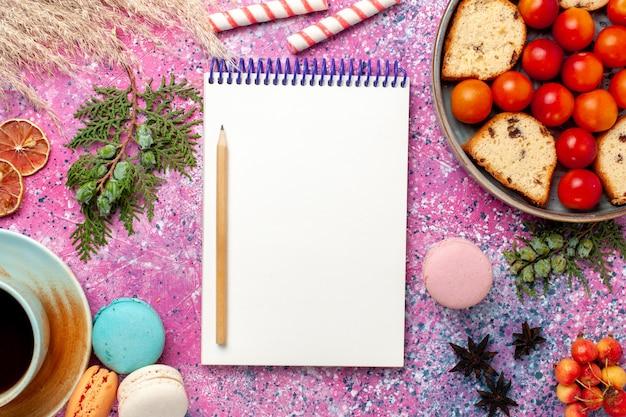 Top vista ravvicinata deliziosa torta a fette con macarons di prugne fresche acide e tè sulla torta rosa scrivania zucchero dolce cuocere biscotti biscotti frutti