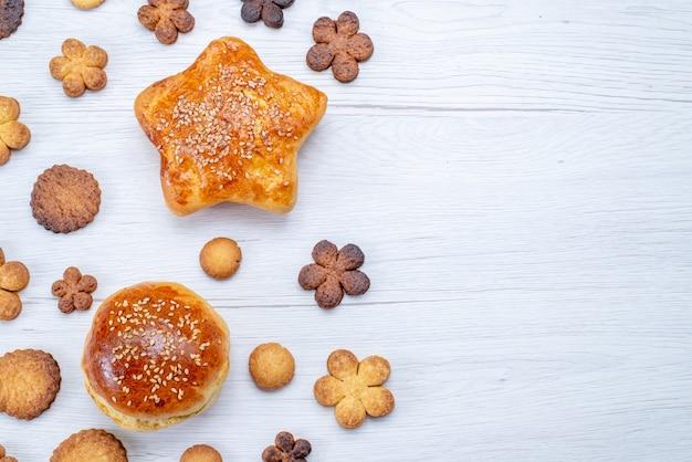 Vista ravvicinata dall'alto di deliziosi pasticcini dolci con biscotti sulla scrivania leggera, zucchero dolce biscotto pasticceria