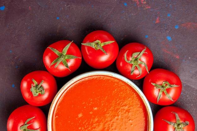 Vista dall'alto ravvicinata deliziosa zuppa di pomodoro circondata da pomodori rossi freschi nello spazio buio