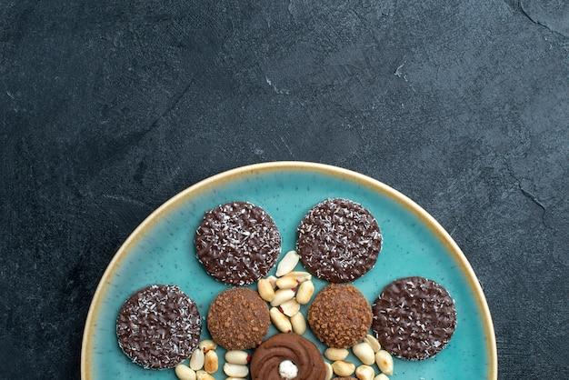 ダークグレーの表面にナッツが入ったさまざまなチョコレートクッキーを上から見る