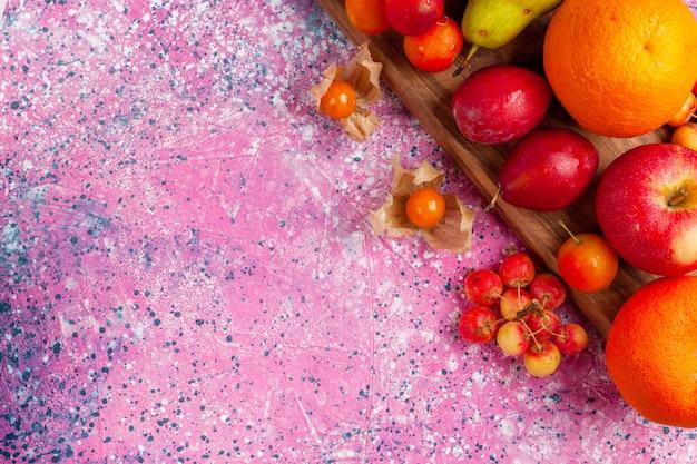Вид сверху крупным планом различные фруктовые композиции свежие и спелые фрукты на розовом фоне.