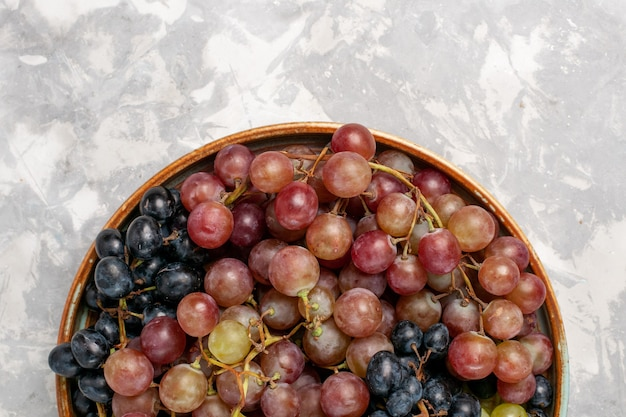 Top vista ravvicinata diverse uve succose mellow aspro frutti su luce bianca scrivania frutta fresca mellow succo di vino