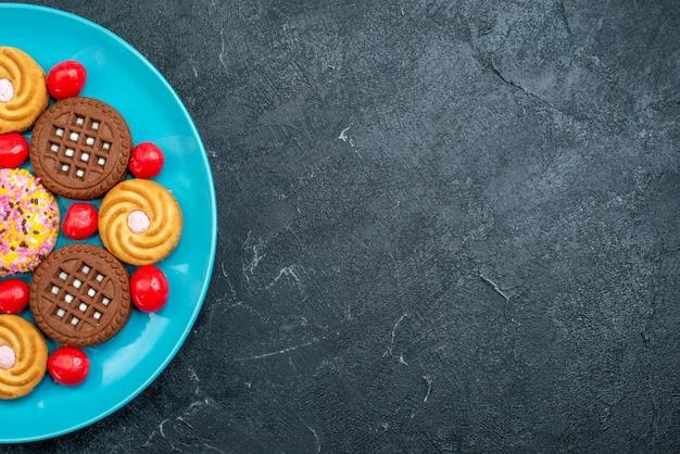 灰色の背景のプレート内のさまざまなシュガークッキーを上から見るキャンディシュガースウィートティークッキービスケット