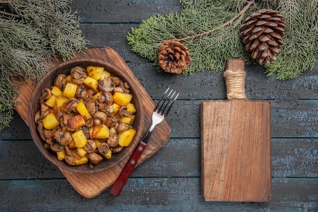 Вид сверху крупным планом блюдо и разделочная доска деревянная миска с картофелем с грибами рядом с разделочной доской и вилкой под еловыми ветками с шишками