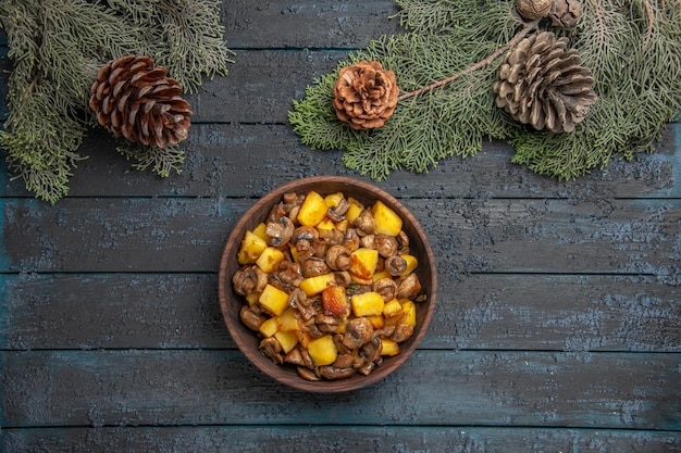 Top close view dish and branches dish of mushrooms and potatoes in the center of the grey table under the spruce branches