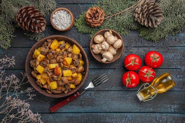 Top close view dish and branches plate of mushrooms and potatoes on the grey table under the spruce branches with cones mushrooms and salt next to the fork tomatoes and oil