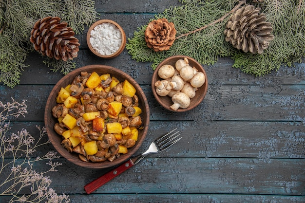 Top close view dish and branches plate of mushrooms and potatoes on the grey table under the spruce branches with cones mushrooms and salt next to the fork