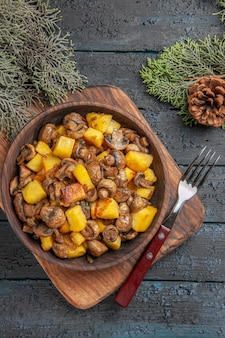 Top close view dish and cutting board wooden bowl of mushrooms and potatoes next to fork and cutting board under spruce branches with cones