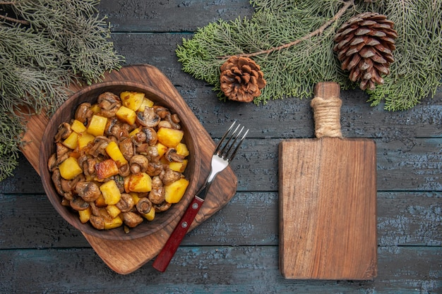 Top close view dish and cutting board wooden bowl of potatoes with mushrooms next to the cutting board and fork under spruce branches with cones