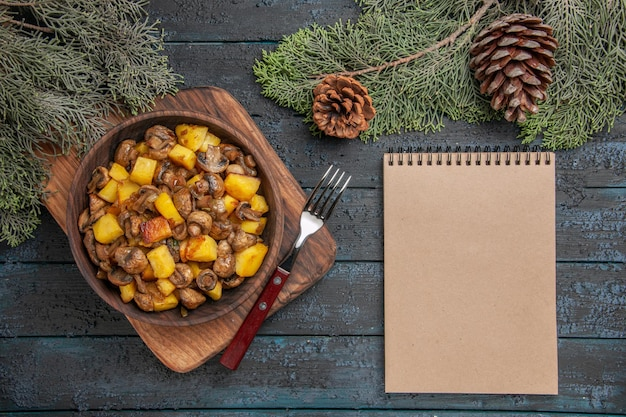 Top close view dish and notebook wooden bowl of potatoes with mushrooms on the cutting board next to the notebook and fork under spruce branches with cones