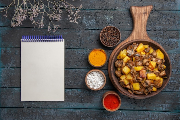 Top close view dish and spices a dish of potatoes and mushrooms on the cutting board and colorful spices around it next to the notebook and branches