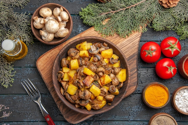 Vista ravvicinata piatto e verdure piatto di patate e funghi a bordo accanto alla forchetta tre pomodori e spezie colorate sott'olio in bottiglia rami di albero e ciotola di funghi