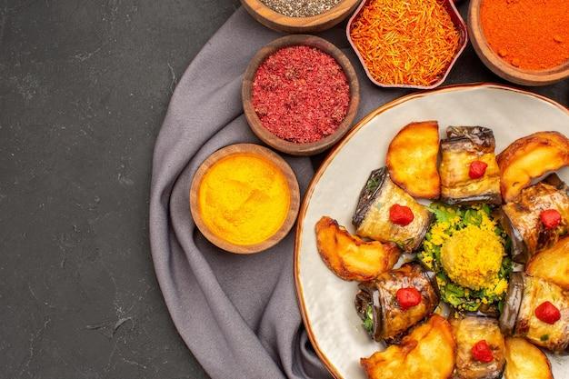 Рулетики из баклажанов, приготовленное блюдо с печеным картофелем и приправами, сверху крупным планом на темном месте