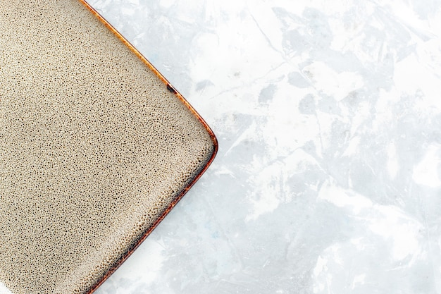 Top vista ravvicinata piatto quadrato vuoto marrone colorato su superficie bianca piatto cucina posate per alimenti in vetro di colore
