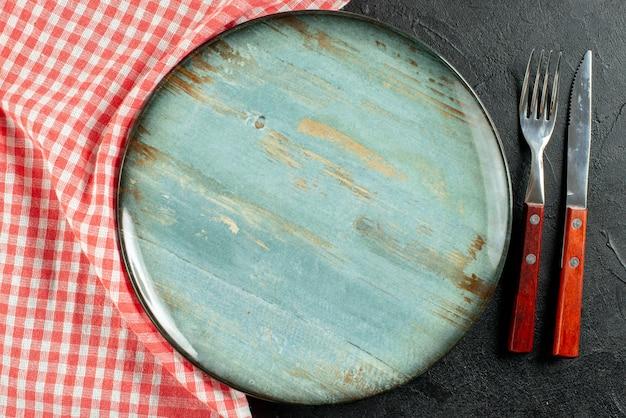 Top vista ravvicinata forchetta e coltello tovagliolo a scacchi bianco rosso piatto rotondo sul tavolo scuro