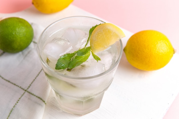Top close view of fresh cold lemonade with ice inside glass along with fresh lemons on the pink surface