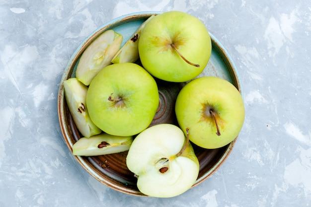 Вид сверху крупным планом нарезанные ломтиками свежие зеленые яблоки и целые фрукты на светлой поверхности. фрукты, свежие спелые спелые пищевые витамины.