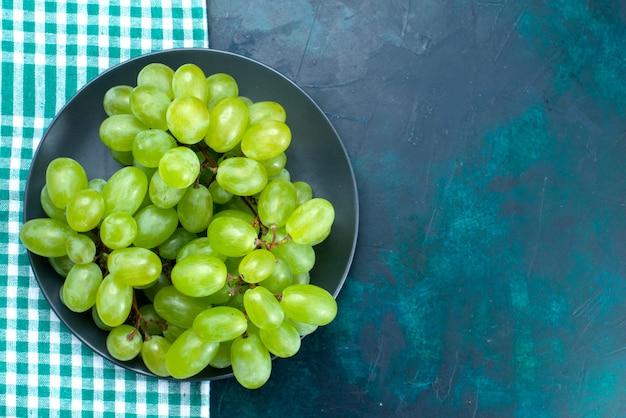 Vista ravvicinata superiore uva verde fresca mellow frutti succosi all'interno del piatto sullo scrittorio blu scuro.