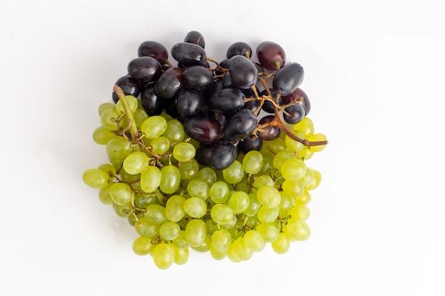 Top vista ravvicinata fresca succosa uva mellow e ed su sfondo bianco