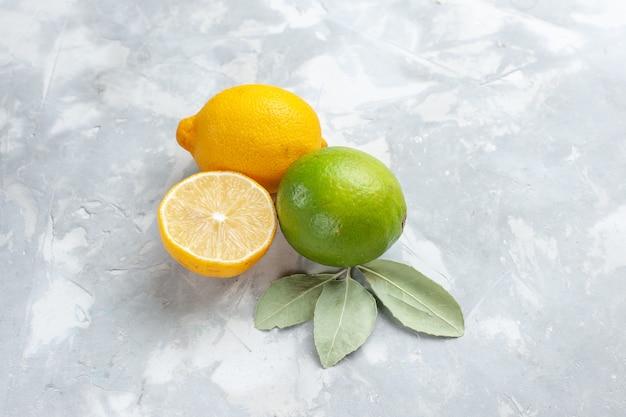 Top vista ravvicinata limoni freschi succosi e aspri sugli agrumi tropicali della frutta esotica dello scrittorio bianco