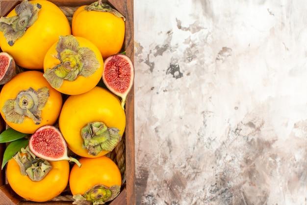 ヌードの背景に木製の箱で新鮮な柿のイチジクを上から見る