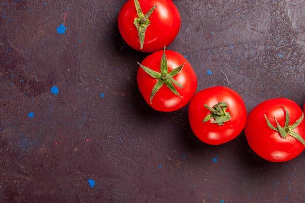 暗いスペースに丸で囲まれた新鮮な赤いトマトを上から見る