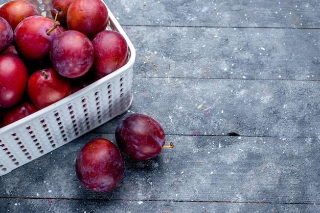 Top vista ravvicinata di prugne fresche acide all'interno del cesto bianco su grigio, frutta fresca acida matura mellow