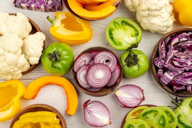 Top vista ravvicinata verdure fresche tagliate pomodori verdi tagliati cavolo rosso tagliato cipolla tagliata zucca cavolfiore tagliato peperone in ciotole su bianco superficie di legno