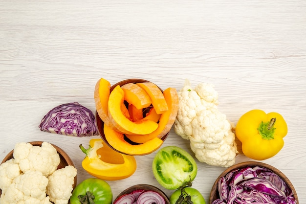 Сверху крупным планом свежие овощи нарезать зеленые помидоры нарезать красную капусту нарезать лук нарезать тыкву цветную капусту нарезать болгарский перец в мисках на поверхности
