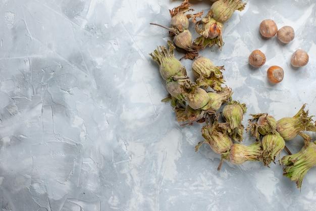 Top vista ravvicinata fresche intere nocciole con bucce su scrivania bianca dado nocciola noce albero pianta