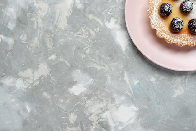 Top vista ravvicinata della torta di frutta con zucchero in polvere su luce, torta di frutta torta da forno dolce