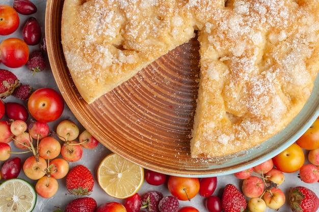 La composizione nella frutta di vista ravvicinata superiore con la torta sulla torta di vitamina fresca matura matura della frutta dello scrittorio bianca cuoce