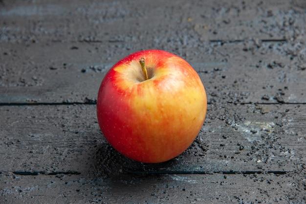 Вид сверху крупным планом фрукты в середине желто-красноватого яблока на сером столе