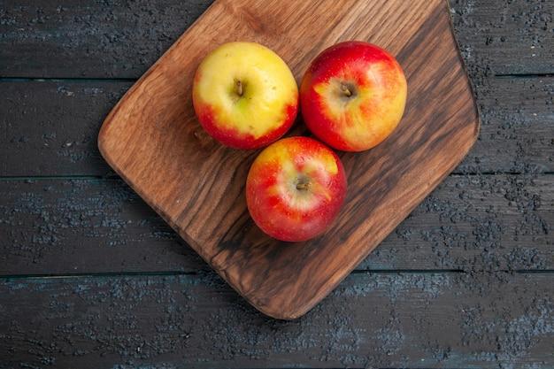 上部のクローズビューは、灰色のテーブルの上の木製のまな板に3つの黄赤リンゴを実らせます