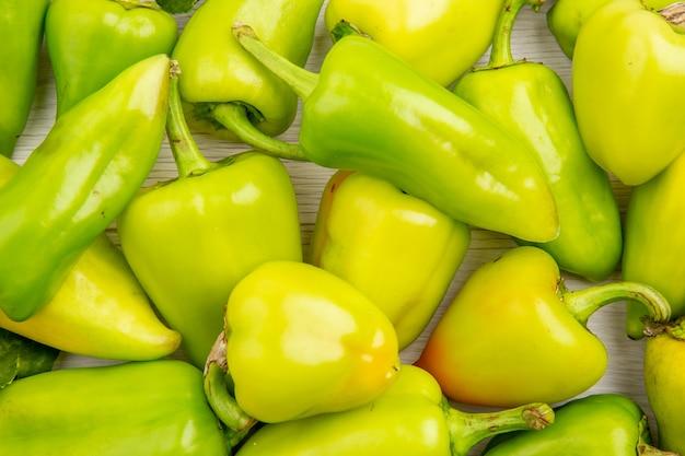 Vista ravvicinata dall'alto peperoni verdi su sfondo bianco colore farina matura pianta foto insalata di peperoni vegetali