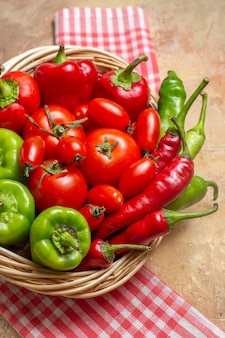 Vista ravvicinata dall'alto peperoni verdi e rossi peperoni piccanti pomodori in cesto di vimini asciugamano da cucina su sfondo ambrato