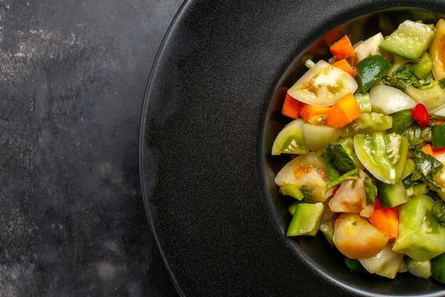 暗い背景の上の黒い楕円形のプレート上のトップクローズビューグリーントマトサラダ