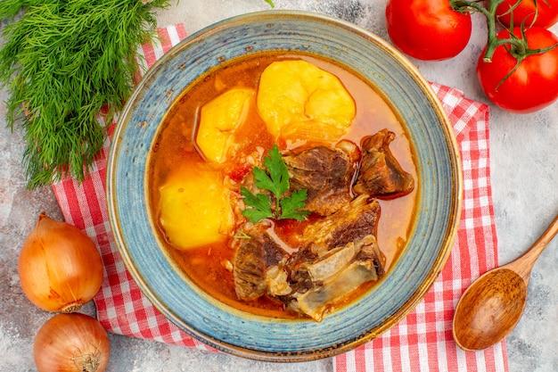 Top vista ravvicinata zuppa di bozbash fatta in casa asciugamano da cucina un mucchio di aneto pomodori cipolle cucchiaio di legno
