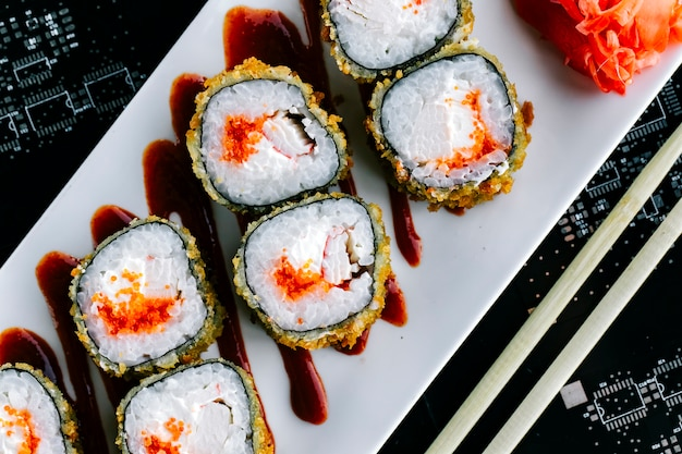 Top close view of hot sushi rolls with red tobiko and crab stick