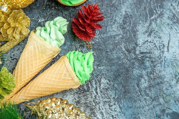 Vista ravvicinata dall'alto gelati albero di natale cupcake ornamenti di natale su sfondo grigio