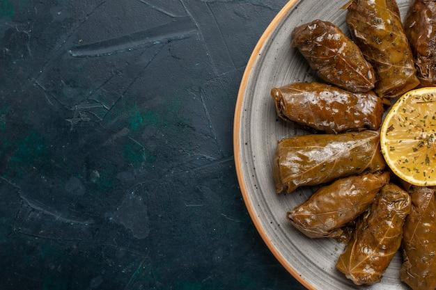 Top vista ravvicinata foglia dolma delizioso pasto a base di carne orientale arrotolato all'interno di foglie verdi sulla scrivania blu scuro