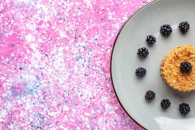 Top close view of little cake with berries on pink surface